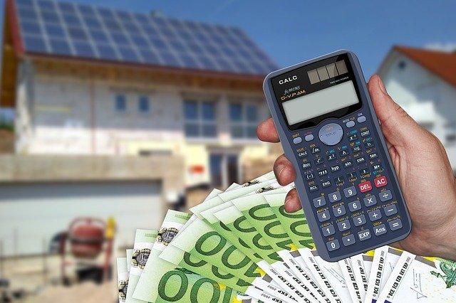 kalkulačka, peníze a budova v pozadí.jpg