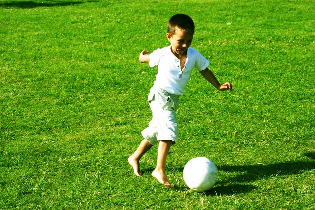 malý kluk v bílém tričku a krátkých kalhotách kope a běží za míčem na trávě