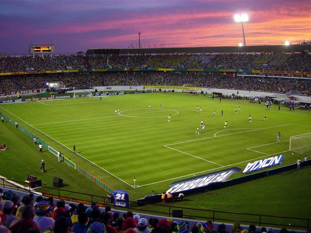 fotbalový stadion, stmívá se, růžová obloha, fotbalisti na hřišti, fanoušci všude po tribunách